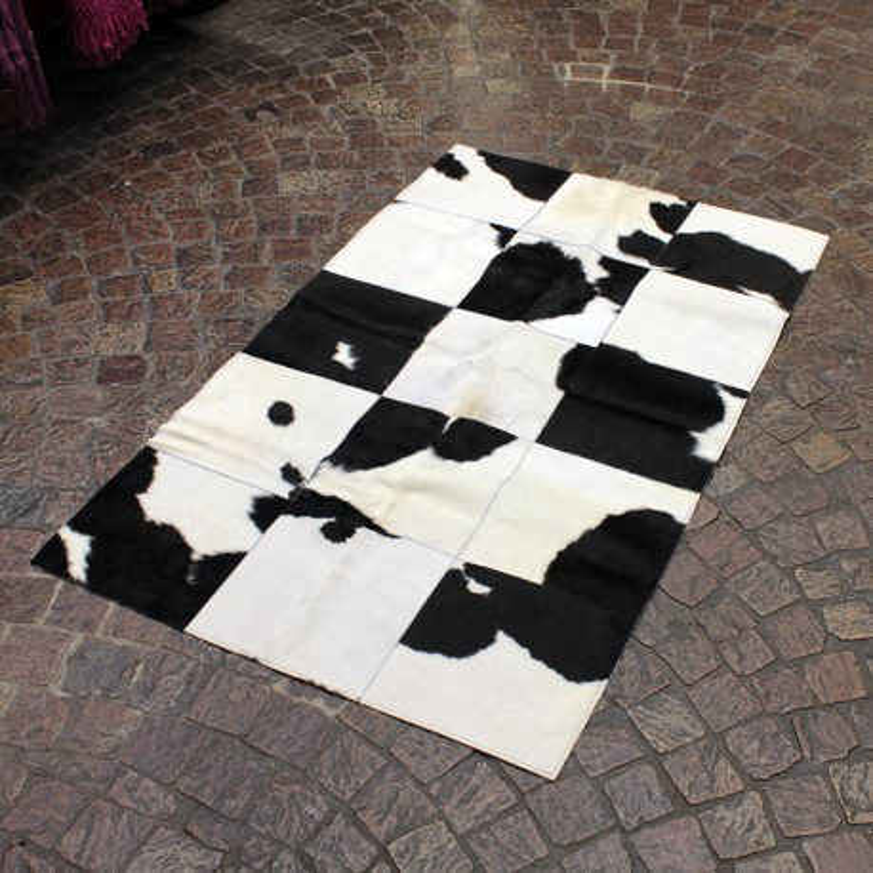Black and white cowhide patchwork bedside rug
